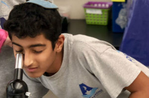 Addlestone Hebrew Academy - Student Looking at Microscope